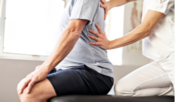 a physiotherapist relieving back pain from a patient