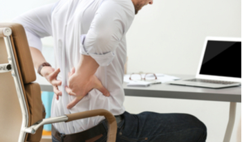 a man holding his back in pain while sitting on his chair at work