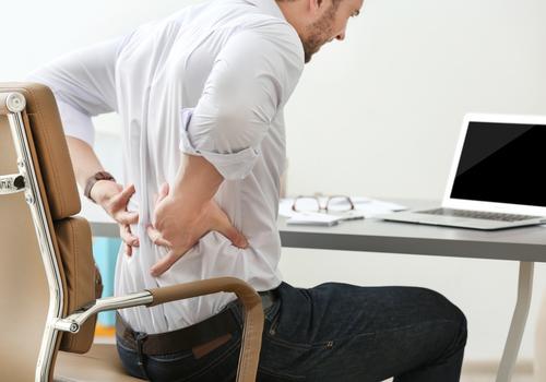 man sits at desk feels back pain