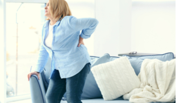 a woman standing up from sitting on her couch holding her back in pain