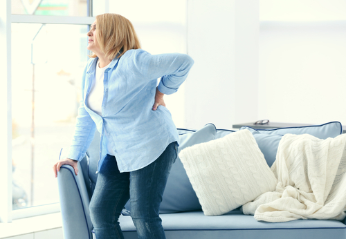 woman getting up from seated position feels back pain