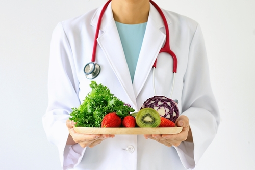 doctor hol;ding plate of healthy food