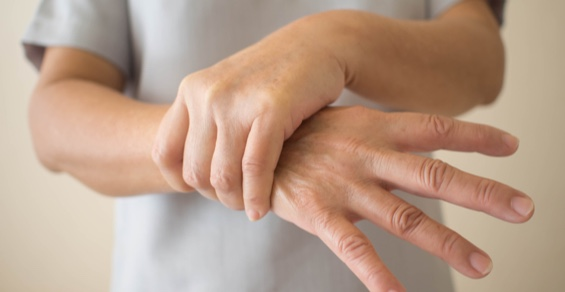 A patient with dystonia holding her wrist in pain