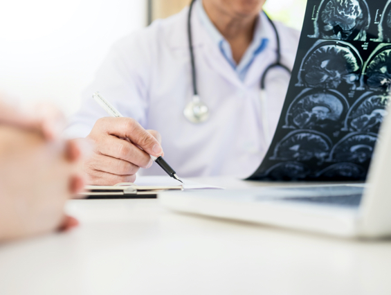A doctor reviews brain scans and takes notes