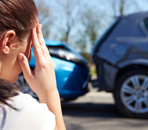 Woman with a concussion holding her head after a car accident