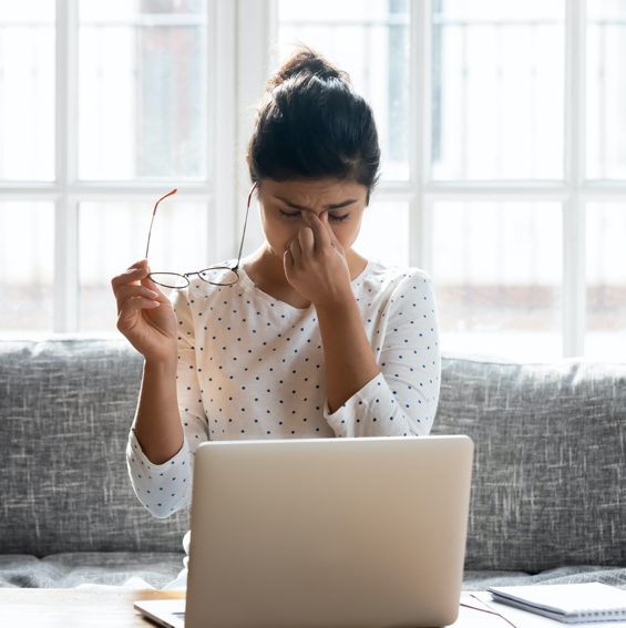 A woman who has suffered multiple concussions has a headache while looking at her computer