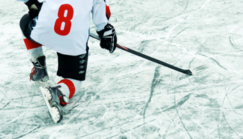 A hockey player taking a knee on the ice