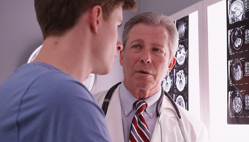 A doctor at Broadview Health Clinic speaks to a patient about his brain scans