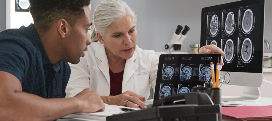 A patient and healthcare provider review brain scan results