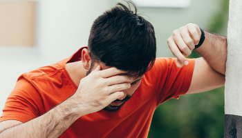 A man leads against the wall in pain after suffering a mild concussion