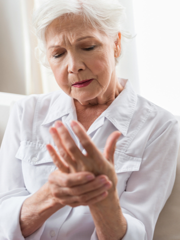 An elderly woman braces her hand while suffering from joint pain