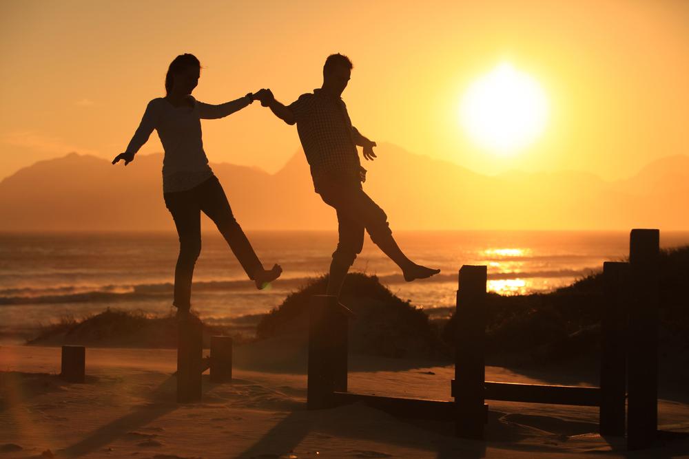 couple balancing on sunset walk