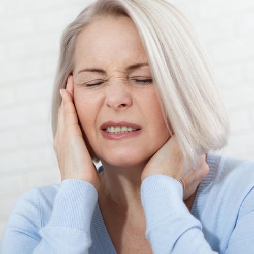 an elderly woman wincing in pain from a headache