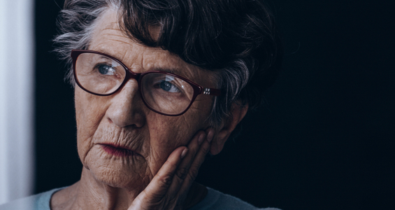 an elderly lady that struggles from Alzheimer's deep in thought