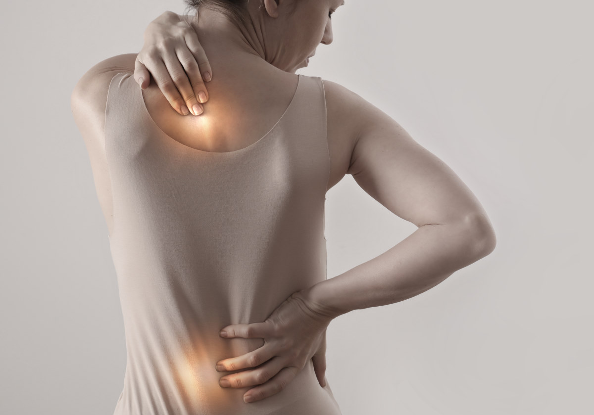 a woman holding her back with the painful areas glowing in yellow