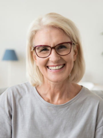 a woman smiling happily after her ear insufflation therapy
