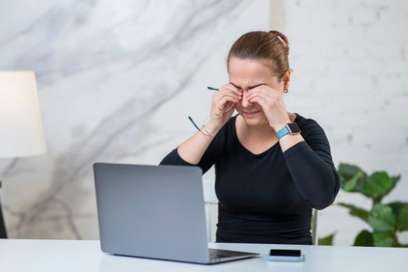 a woman struggling at work because she didn't know the standard concussion recovery time and went back to work too early